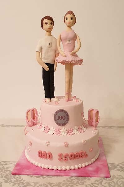 Pink cake with female and male dancers on top