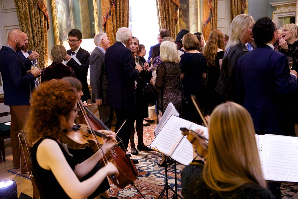 String quarter in foreground. Guests mingling in the background.