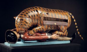 Wooden sculpture of tiger attaching soldier.