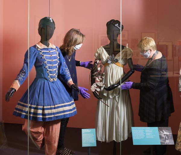 Curators Eleanor and Jane install Adeline Genée's Dryad costume with Tamara Karsavina's costume for Les Cantinières on the left